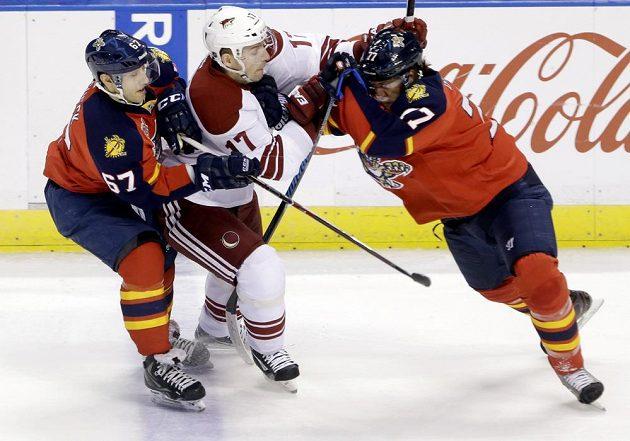 Radim Vrbata (17) z Phoenixu se snaží přejít přes dvojici bránících hokejistů Floridy Vincenta Trochecka (67) a Toma Gilberta (77).