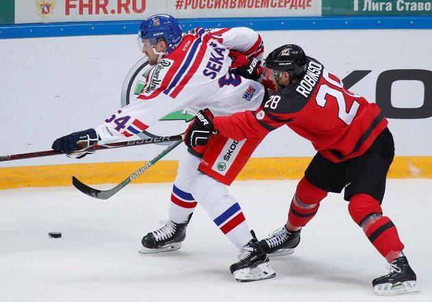 Jiří Sekáč brání puk před Matem Robinsonem v uktání Česka s Kanadou na Channel One Cupu v Moskvě.