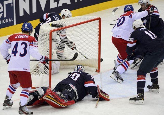 Český reprezentant Tomáš Rolinek (vpravo) střílí gól. Vlevo je Dále na snímku jsou český reprezentant Jan Kovář (vlevo), americký brankář Tim Thomas (ležící) a Jimmy Hayes z USA (druhý zprava).