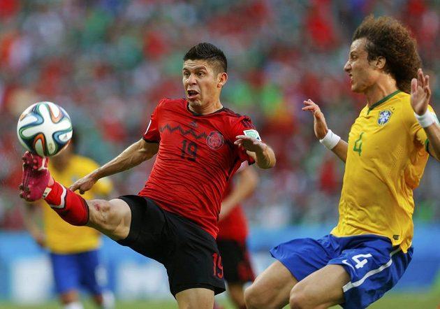 Mexický kanonýr Oribe Peralta (vlevo) v souboji o míč s Davidem Luizem.