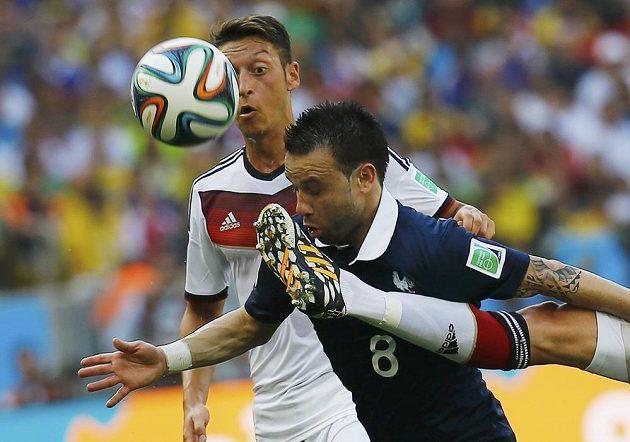 Mathieu Valbuena (uprostřed) se pere o míč s německou přesilou Mesut Özil (vzadu) a Benedikt Höwedes.
