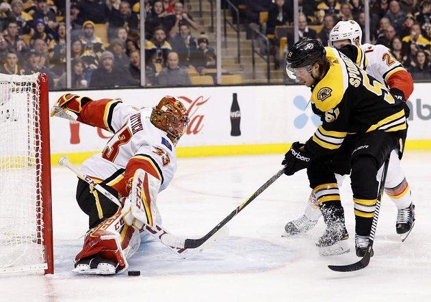 Brankář Calgary Flames David Rittich likviduje šance bostonského Ryana Spoonera v utkání NHL.
