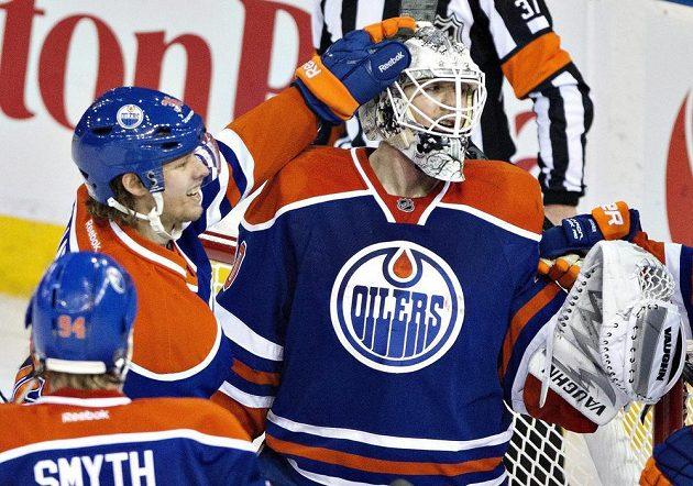Hokejisté Edmontonu Ryan Smyth (číslo 94) a Philip Larsen (uprostřed) gratulují Benu Scrivensovi k zákroku v utkání proti San Jose.