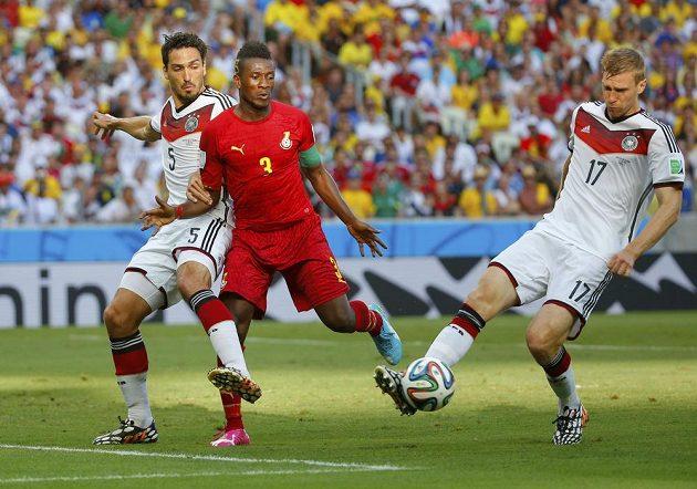 Asamoah Gyan z Ghany (uprostřed) dotírá na německého obránce Pera Mertesackera, který se pokouší uklidit míč do bezpečí.