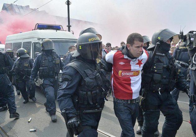 Slávista, kterého odvádí policie, se zřejmě na derby nepodívá.