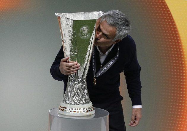 José Mourinho už s medailí na krku líbá trofej pro vítěze Evropské ligy.