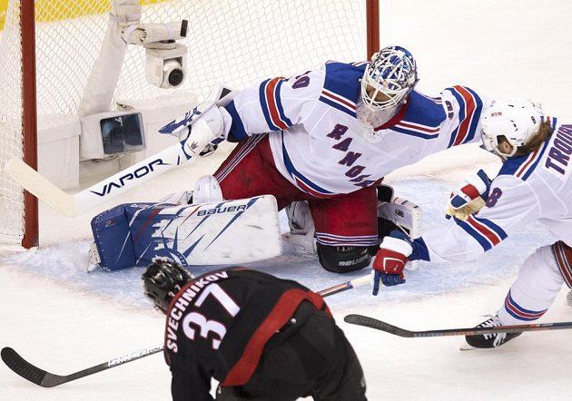 Ruský křídelník Caroliny Andrej Svečnikov překonává gólmana New York Rangers Henrika Lundqvista a završuje hattrick, zákrok obránce Jacoba Trouby už přišel pozdě.
