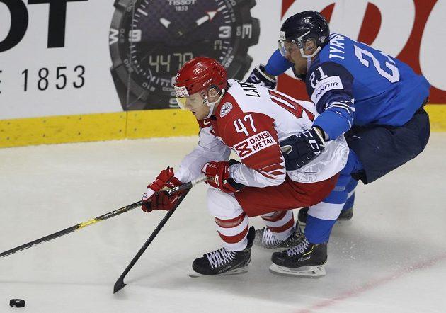 Finský hokejista Juhani Tyrvainen (vpravo) v souboji s Dánem Oliverem Larsenem během utkání mistrovství světa.