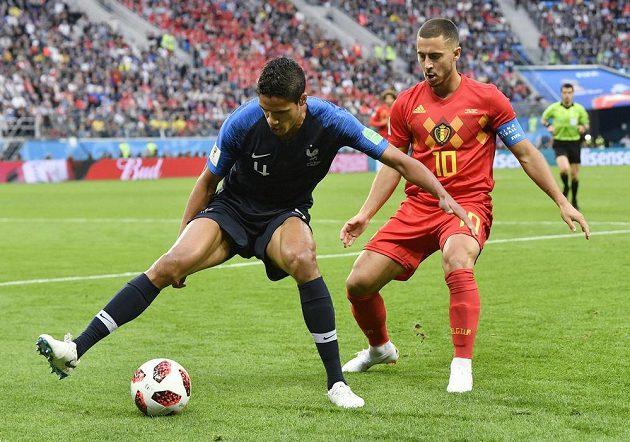 Francouzský zadák Raphaël Varane (vlevo) střeží režiséra hry belgického týmu Edena Hazarda.