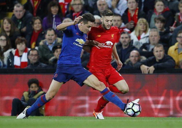 Záložník Manchesteru United Ander Herrera bere míč střídajícímu Adamu Lallanovi z Liverpoolu.