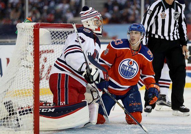 Útočník Edmontonu Ryan Nugent-Hopkins před brankářem Winnipegu Connorem Hellebuyckem.