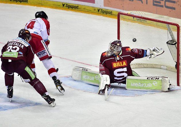 Olomoucký hokejista Vilém Burian střílí gól brankáři Sparty Matěji Machovskému. Vlevo je Jan Košťálek ze Sparty.