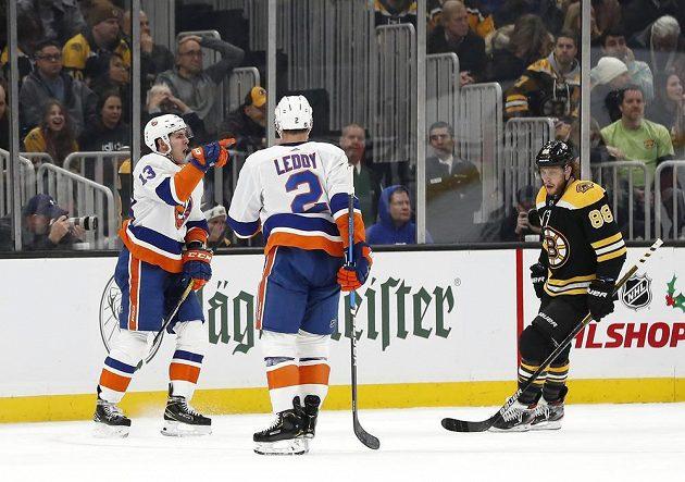 Hokejisté Islanders se radují z branky, David Pastrňák smutně přihlíží