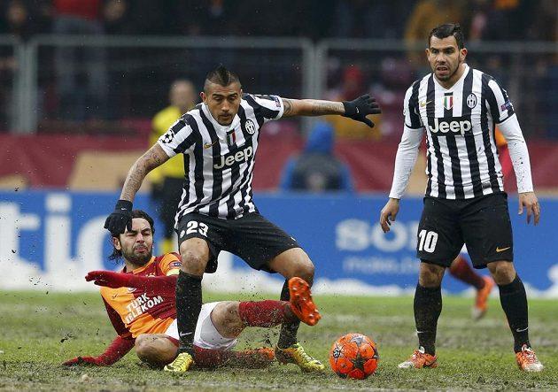 Fotbalisté Juventusu Arturo Vidal (uprostřed) a Carlos Tévez (vpravo) v souboji se Selcukem Inanem z Galatasaraye Istanbul.