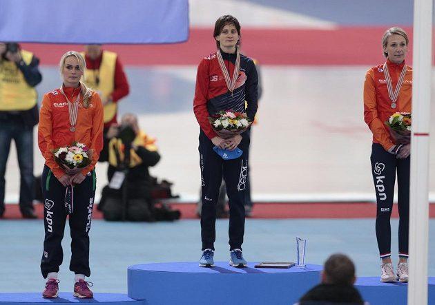 Martina Sáblíková na nejvyšším stupínku při medailovém ceremoniálu na MS po závodě na 5 km. Vlevo broznová Irene Schoutenenová, vpravo stříbrná Carien Kleibeukerová.