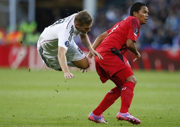 Posila Realu Madrid Toni Kroos padá po souboji s útočníkem Sevilly Carlosem Baccou.