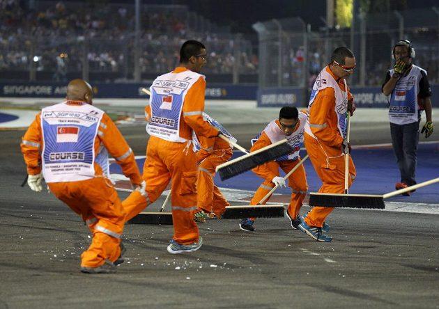 Traťoví stewardi se činí při úklidu úlomků vozu po havárii Nika Hülkenberga.