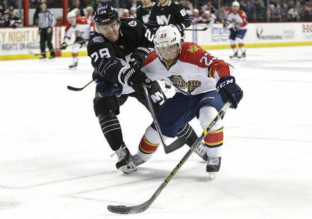 Obránce New Yorku Islanders Marek Židlický (28) a floridský Rocco Grimaldi (23) v souboji o puk v úterním duelu NHL.