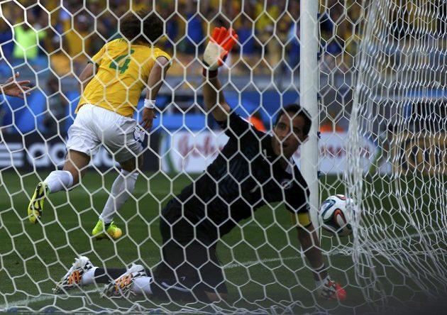 Brankář Chile Claudio Bravo loví míč ze sítě, zatímco Brazilec David Luiz běží slavit vstřelený gól.