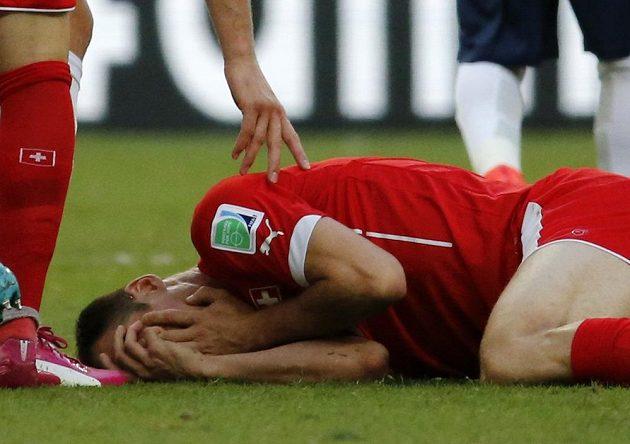 Švýcarský obránce Steve von Bergen leží na zemi po střetu s francouzským útočníkem Giroudem.