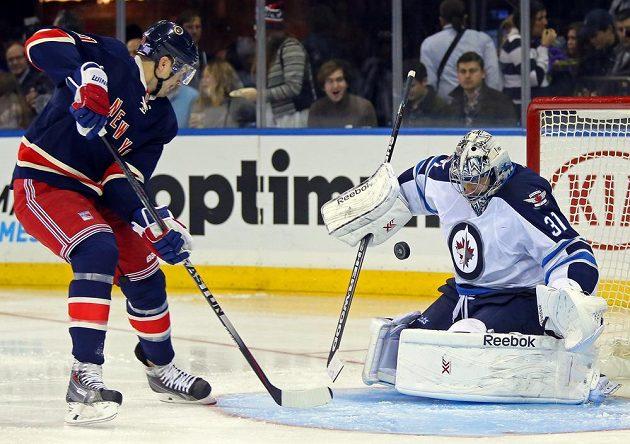 Brankář Winnipegu Ondřej Pavelec kryje střelu Ricka Nashe z NY Rangers.