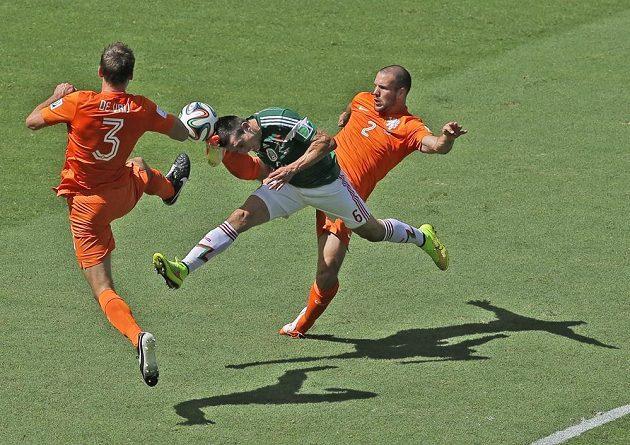 Mexičan Héctor Herrera v osmifinálovém duelu na MS zkouší prorazit nizozemským dvojblokem, který tvoří Stefan de Vrij (vlevo) a Ron Vlaar.