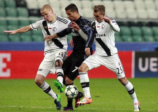 Cristiano Ronaldo z Realu Madrid (uprostřed) se snaží protáhnout mezi dvojicí Adam Hloušek (vlevo), Jakub Rzezniczak z Legie Varšava.