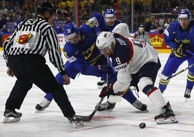 Americký hokejista Andrew Copp bojuje o puk po vhazování se Švédem Eliasem Lindholmem během utkání mistrovství světa v Kolíně nad Rýnem.
