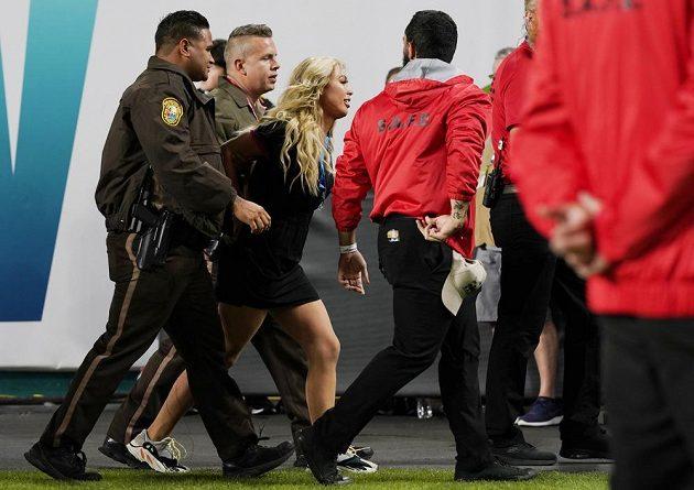 Členové ochranky odvádějí mladou dívku, která se během Super Bowlu pokusila vtrhnout na hřiště.