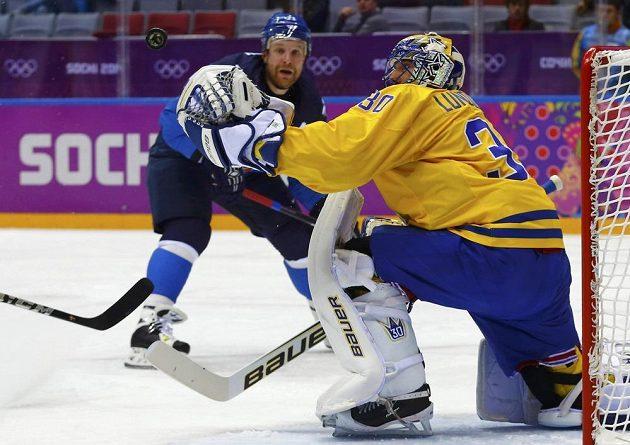Finský útočník Leo Komarov ohrožuje švédského brankáře Henrika Lundqvista.