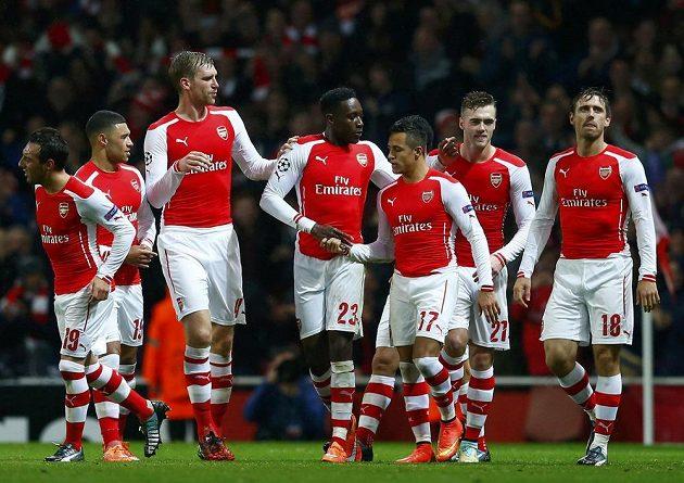Alexis Sánchez (uprostřed) přijímá gratulace od spoluhráčů z Arsenalu ke gólu proti Anderlechtu ve 4. kole Ligy mistrů.