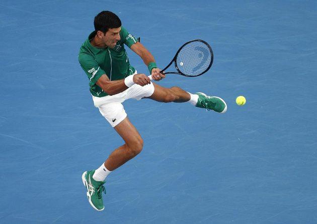 Srb Novak Djokovič při jednom z akrobatických zákroků proti Rogeru Federerovi ze Švýcarska.