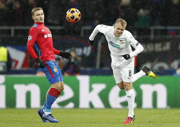 Forward CSKA Moskva Fjodor Čalov (vlevo) sleduje, jak plzeňský obránce David Limberský hlavou odvrací míč v utkání Ligy mistrů.