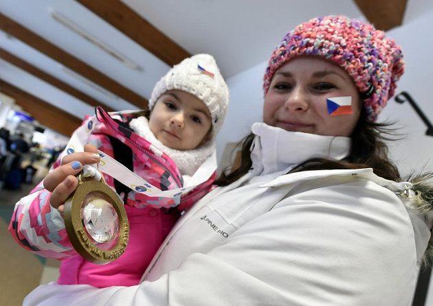 Čtyřletá Kristínka Doležalová z Prahy (na snímku s maminkou) se zlatou medailí, kterou jí daroval vítěz závodu Martin Fourcade z Francie.