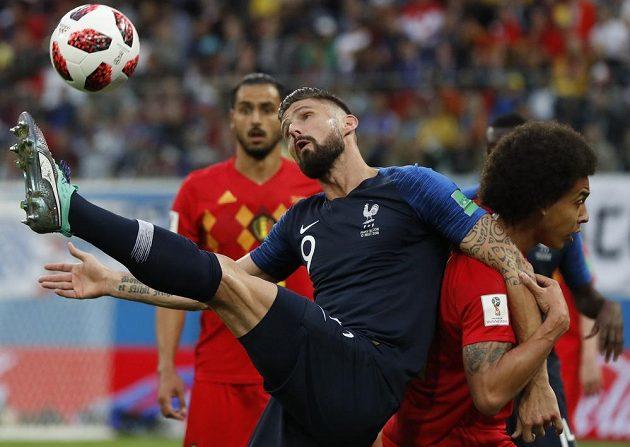Francouzský útočník Olivier Giroud bojuje s belgickou obranou.