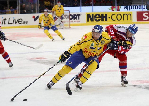 Alexander Johansson a Jan Rutta v souboji na Švédských hokejových hrách mezi domácím týmem a českým výběrem.