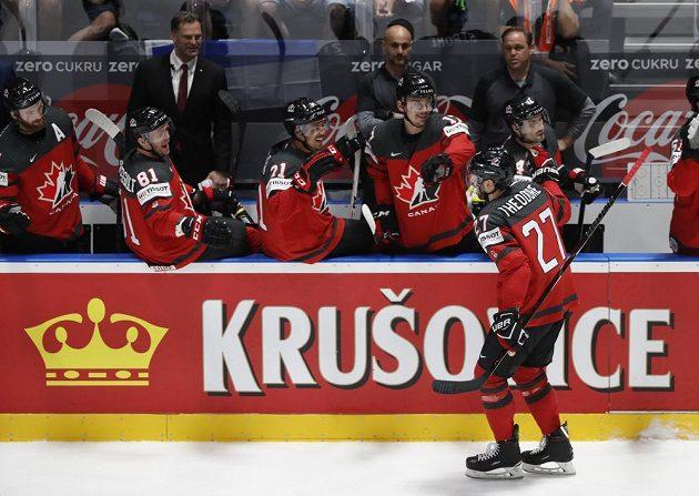 Kanaďan Shea Theodore slaví se spoluhráči vedoucí gól ve finále MS.