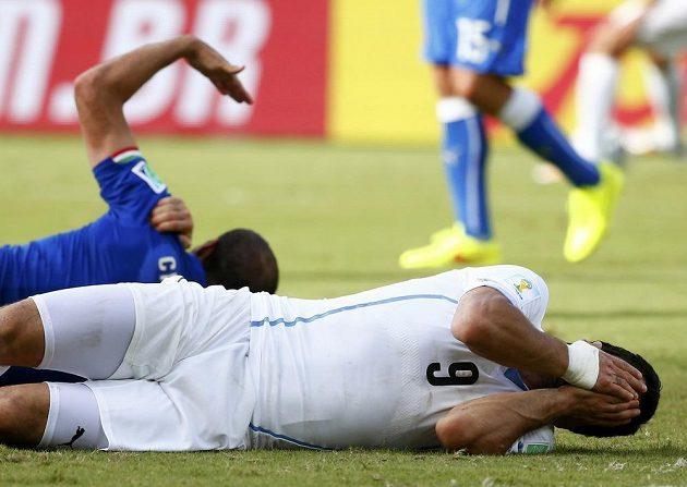 Italský obránce Giorgio Chiellini si drží rameno, uruguayský snajpr Luis Suárez (vpředu) zase obličej. Bude za kousnutí soupeře potrestán?