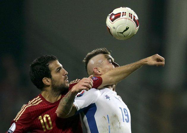 Španěl Cesc Fabregas (vlevo) ve vzdušném souboji o míč s Jurajem Kuckou.