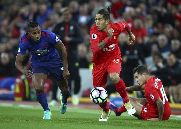 Záložník Liverpoolu Roberto Firmino se rozhlíží komu nahraje, obránce Manchesteru United Eric Bailly nestíhá.