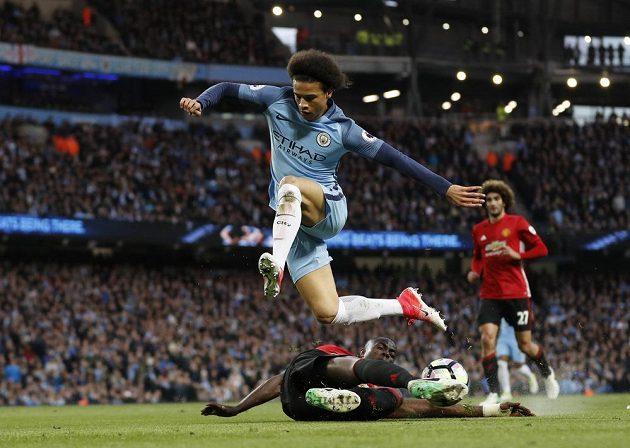 Leroye Saneho z Manchesteru City zastavuje skluzem Eric Bailly.