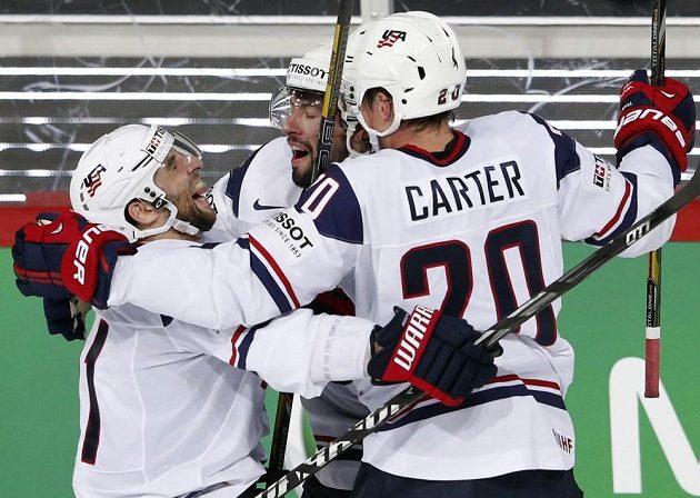 Američan Nate Thompson (uprostřed) slaví svoji trefu ve čtvrtfinále MS proti Rusku v objetí spoluhráčů Stephena Gionty (vlevo) a Ryana Cartera.
