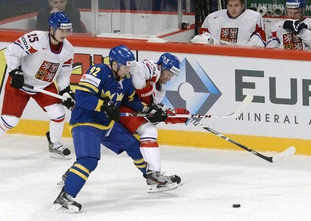Český útočník Jiří Hudler (vlevo) sleduje souboj mezi švédským forvardem Gabrielem Landeskogem a Jiřím Tlustým.