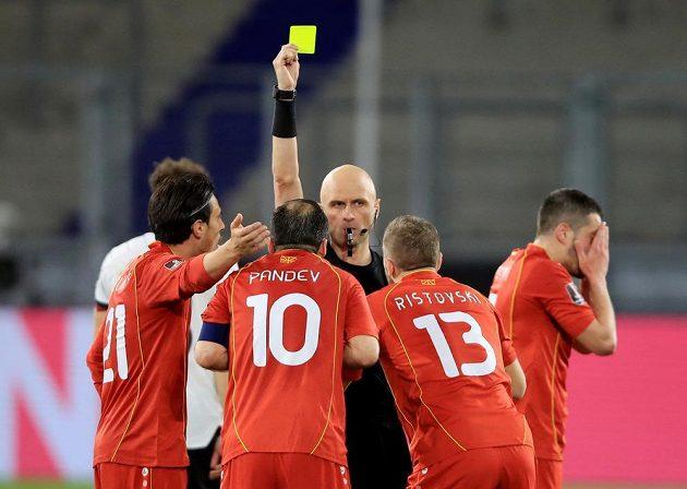 Fotbalista Severní Makedonie Goran Panděv vidí žlutou kartu v utkání kvalifikace MS 2022 s Německem.