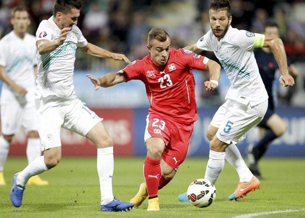 Švýcar Xerdan Shaqiri (uprostřed) si vede míč mezi Bostjanem Cesarem (vpravo) a Andrazem Kirmem ze Slovinska.