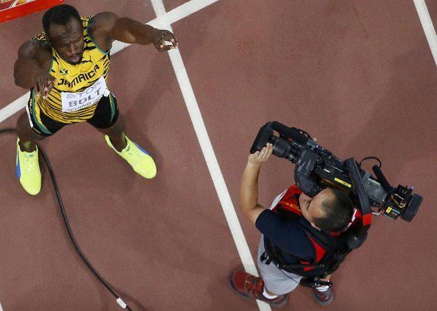 Kameraman snímá Usaina Bolta po vítězném závodě na 200 metrů.