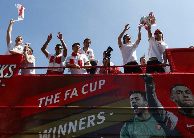 Tomáš Rosický (druhý zprava) a Jack Wilshere s trofejí pro vítěze FA Cupu během triumfální jízdy Arsenalu Londýnem.