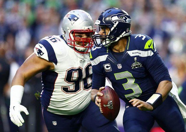 Quarterback Russell Wilson (vpravo) z týmu Seattle Seahawks se snaží uniknout Sealveru Siligovi z týmu Patriotů.