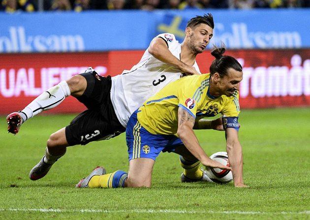 Švédská hvězda Zlatan Ibrahimovic (ve žlutém) na kolenou, kam ho dostal Rakušan Aleksandar Dragovič.