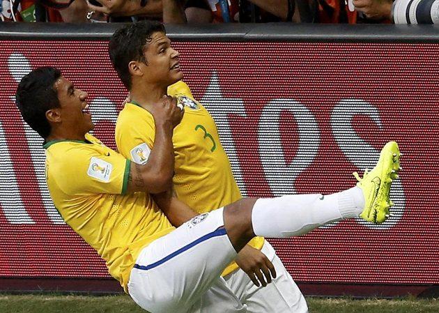 Paulinho (vlevo) jásá se střelcem brazilského gólu Thiagem Silvou.